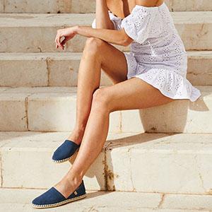 Marinblåa espadrillos på kvinna i vit klänning.